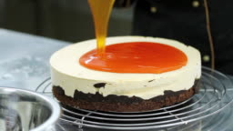 A confectioner adding an orange topping over a cake