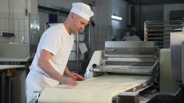 vídeos y material grabado en eventos de stock de confectioner kneading pastry dough in bakery - un solo hombre maduro