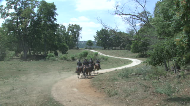 a confederate cavalry regiment gallops along a dirt road during the civil war. - war stock-videos und b-roll-filmmaterial