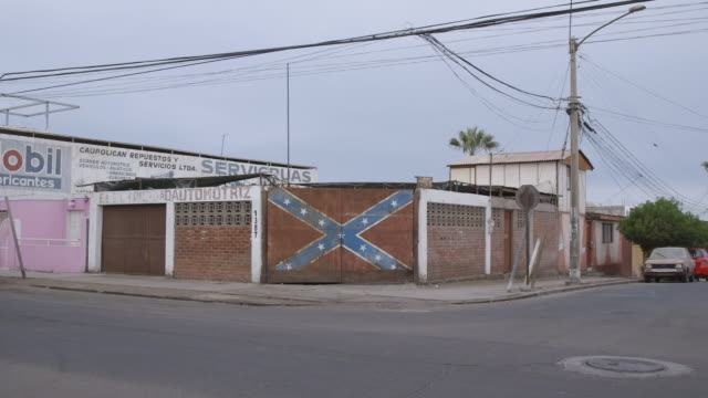 confederate flag painted over garage door of chilean auto shop - confederate flag stock videos & royalty-free footage