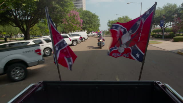 vídeos de stock e filmes b-roll de confederate flags flying on back of truck driving down highway, motorcycle follows - bandeira