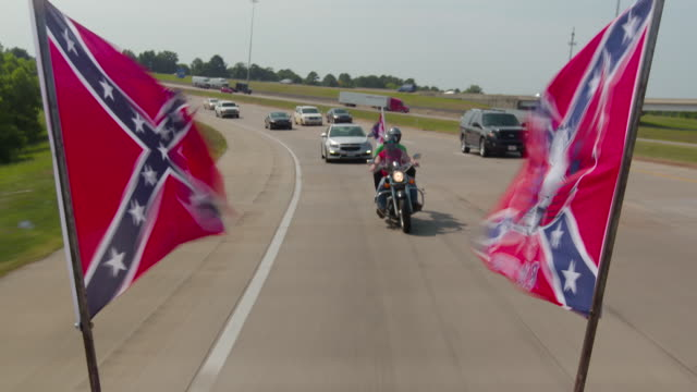 confederate flags flying on back of truck driving down highway, motorcycle follows - confederate flag stock videos & royalty-free footage