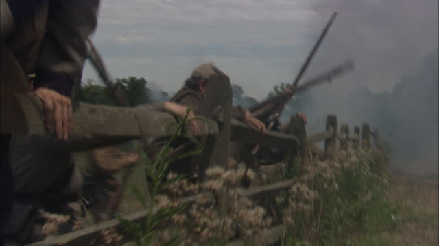 confederate soldiers climb a fence and take fire in a civil war reenactment. - bürgerkrieg stock-videos und b-roll-filmmaterial
