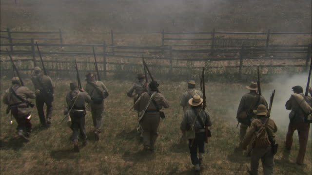confederate soldiers flee across a field and climb over a fence during a civil war battle. - gettysburg stock videos & royalty-free footage