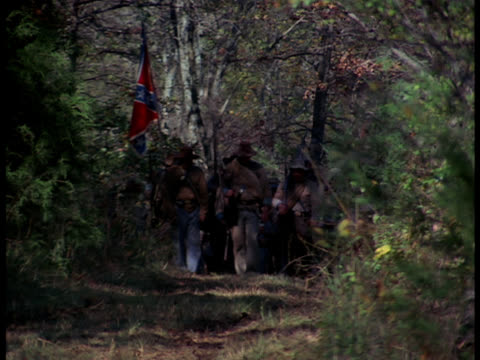 Confederate soldiers march through the forest.
