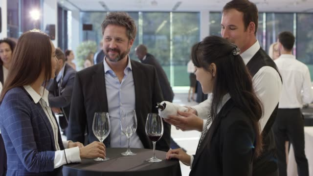 conference attendees chatting at the table in the lobby of the conference center and drinking a glass of wine - service stock videos & royalty-free footage