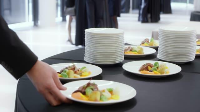 vídeos y material grabado en eventos de stock de asistentes a la conferencia tomar placas con plato principal de la mesa de la cocina - descanso para comer