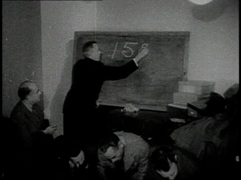stockvideo's en b-roll-footage met conference of men in suits gathering around speaker / man writing on a blackboard behind other men leaning over table / recruits marching up street /... - zij aan zij