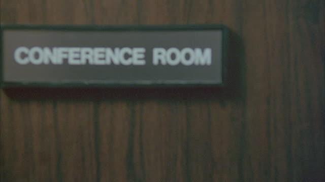A conference room door closes.