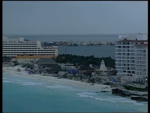 Conference welcome banner Road sign to WTO conference TGV Cancun beach hotels buildings on foreshore GV Boat at sea TGV Cancun beach under overcast...