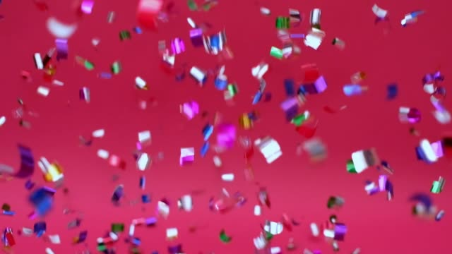 Confetti falling against cherry red background