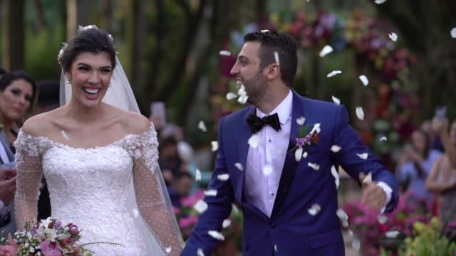 vídeos de stock, filmes e b-roll de confetti que joga em pares recém-casado felizes - casamento