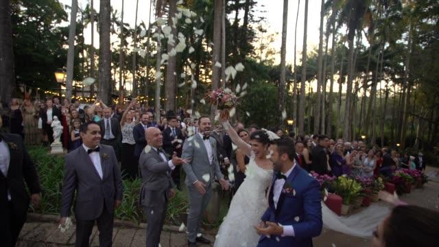 vídeos de stock, filmes e b-roll de confetti que joga em pares recém-casado felizes - bride