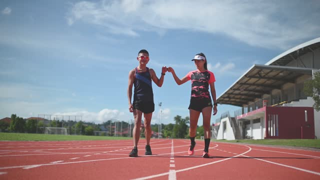 confidence and satisfied athlete walking and giving a fist bump on all-weather-track and field stadium in the morning - running track stock videos & royalty-free footage