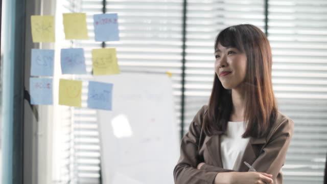 confidence businesswoman che scrive un'idea su una nota per il nuovo progetto - note pad video stock e b–roll