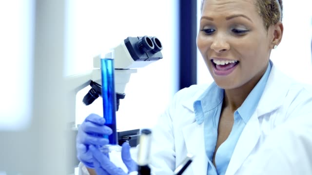 Confident African American female scientist discusses findings with research assistant