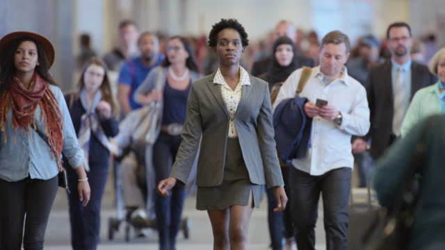 SLO MO. Confident African-American businesswoman walks ahead of a crowd in busy airport terminal.