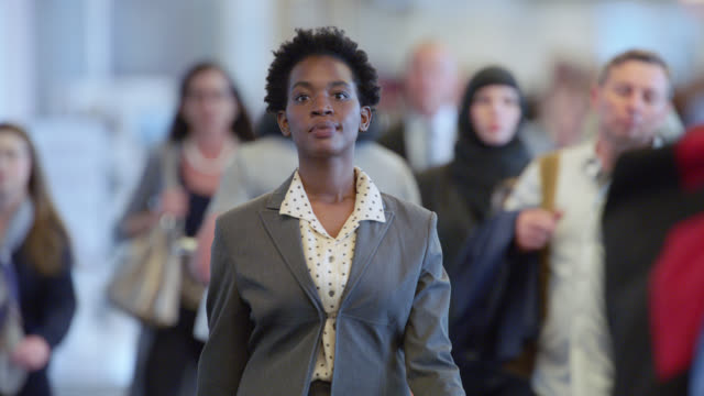 SLO MO. Confident African-American businesswoman walks through crowded terminal in airport.