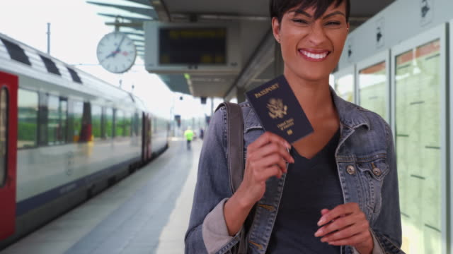 confident african-american female shows camera her passport at train station - passport stock videos & royalty-free footage