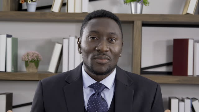vidéos et rushes de un gars afro-américain confiant porter costume parler et regarder la caméra dans son bureau. - interview