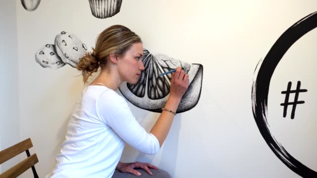 confident and concentrated artist finishing up her mural artwork - mural stock videos & royalty-free footage