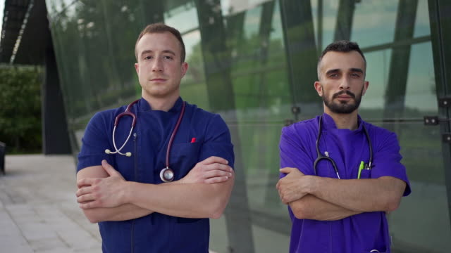 confident anestesiologists proudly stand in front of modern medical clinic after their long shift - side by side stock videos & royalty-free footage