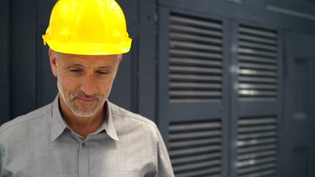 Confident architect wearing hardhat in office