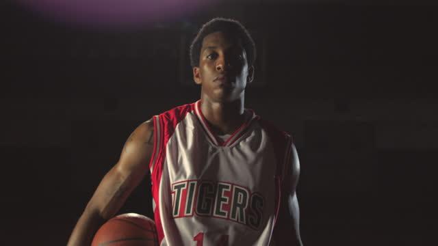 A confident basketball player dribbles a ball at center court.