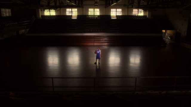 vídeos de stock, filmes e b-roll de a confident basketball player in uniform walks onto an empty court - quadra esportiva