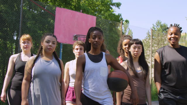 confident basketball team walking on sports court - potere femminile video stock e b–roll