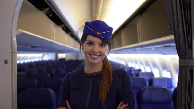 confident beautiful air stewardess looking at camera smiling with arms crossed at the air plane - crew stock videos & royalty-free footage