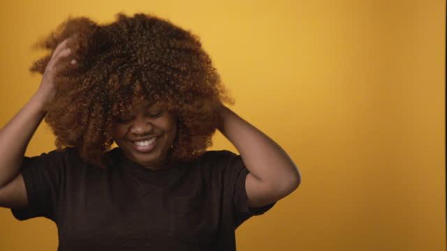 vídeos de stock, filmes e b-roll de confiante, linda, sorridente, profissional, jovem afro-americana feliz brincando com seu cabelo afro na frente de um fundo amarelo-colorido de mostarda brilhante com espaço de cópia - afro americano