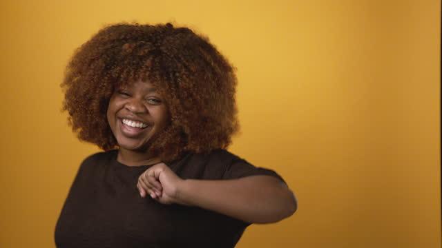 vídeos y material grabado en eventos de stock de confiada, hermosa, sonriente, profesional, feliz joven afroamericana bailando frente a un brillante fondo amarillo mostaza con espacio de copia - waist up