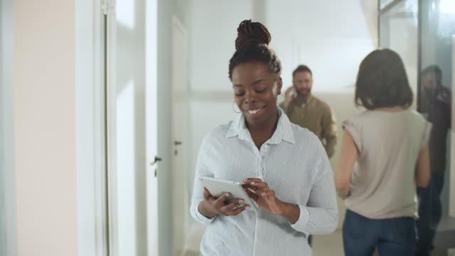 Zuversichtlich schwarz Geschäftsfrau Büro Korridor entlang