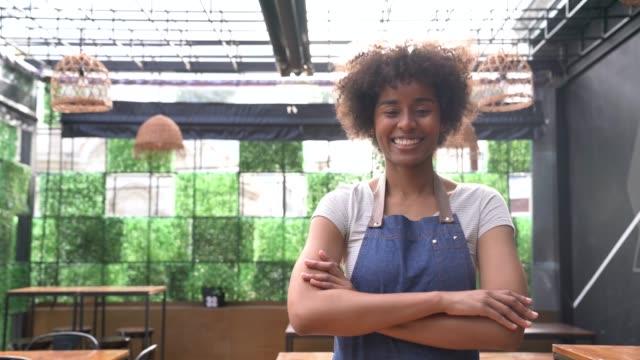 vertraute schwarze geschäftsinhaberin eines restaurants mit blick auf die kamera lächelnd - gastwirt stock-videos und b-roll-filmmaterial