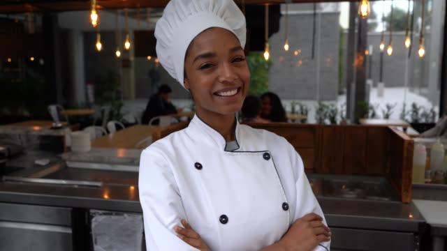 selbstbewusste schwarze köchin lächelnd in der kamera mit gekreuzten armen - gourmet küche stock-videos und b-roll-filmmaterial
