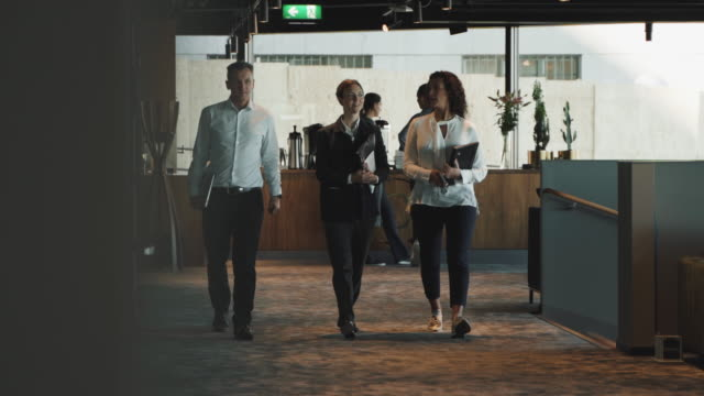 confident business colleagues talking while walking at creative office cafeteria - inside of stock-videos und b-roll-filmmaterial