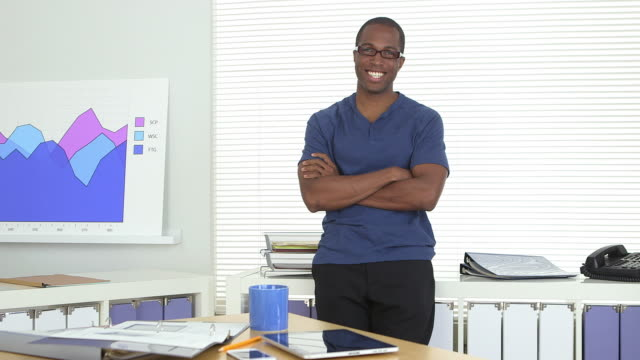 Confident business man crossing arms in office