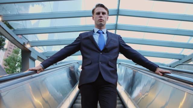 confident businessman descending escalator - assertiveness stock videos & royalty-free footage