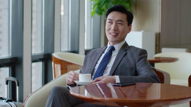 vídeos de stock, filmes e b-roll de confident businessman drinking coffee in airport lounge,4k - café bebida