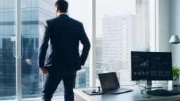 Confident Businessman in a Suit Contemplating Business Deal in His Office, Stands up from His Desk and Walks to a Window to Think. Window Has Panoramic View on Big City Business District.