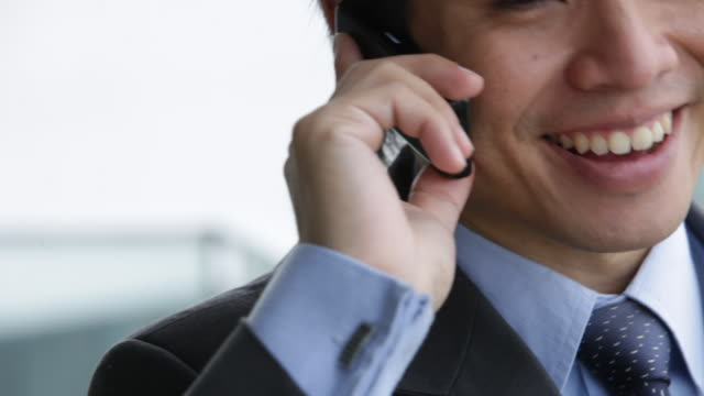 a confident businessman talks on his cell phone in his office. - 25 29 years stock videos & royalty-free footage