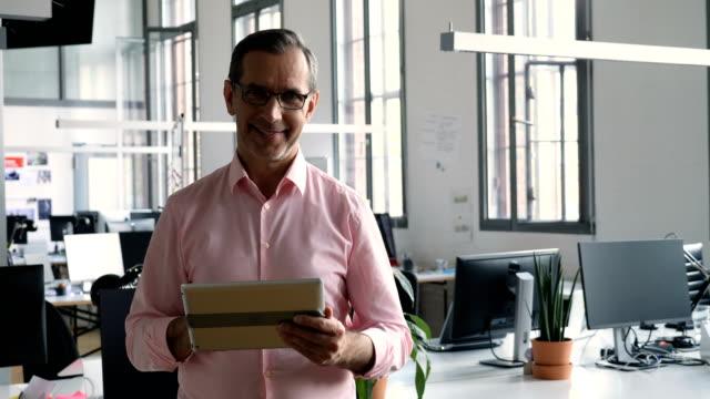 Confident businessman using digital tablet