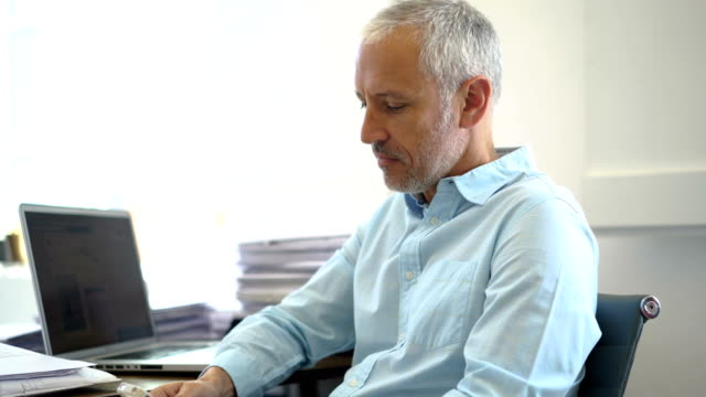 Confident businessman using mobile phone at desk