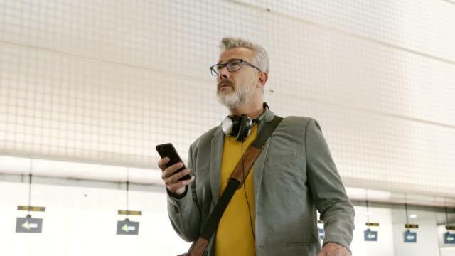 vídeos de stock, filmes e b-roll de homem de negócios confiável que usa o telefone esperto no aeroporto - panning