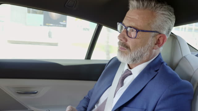 confident businessman using smart phone in car - 50 54 years stock videos & royalty-free footage