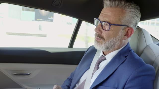 zuversichtlicher geschäftsmann mit smartphone im auto - 50 54 jahre stock-videos und b-roll-filmmaterial