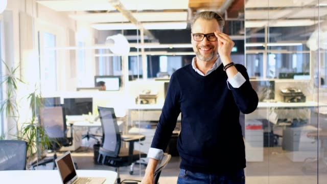 confident businessman wearing eyeglasses in office - rivolto verso l'obiettivo video stock e b–roll