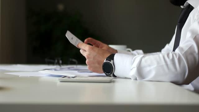 vídeos de stock e filmes b-roll de confident businessman wearing suit reading paper letter sitting at desk - capital letter
