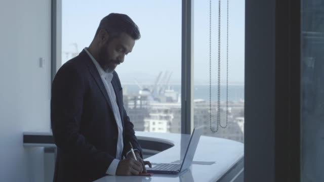 confident businessman writing note at desk - ジャケット点の映像素材/bロール
